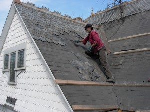 Russell Voss with Easterday Construction using a Slate Ripper to remove old slate from the roof.